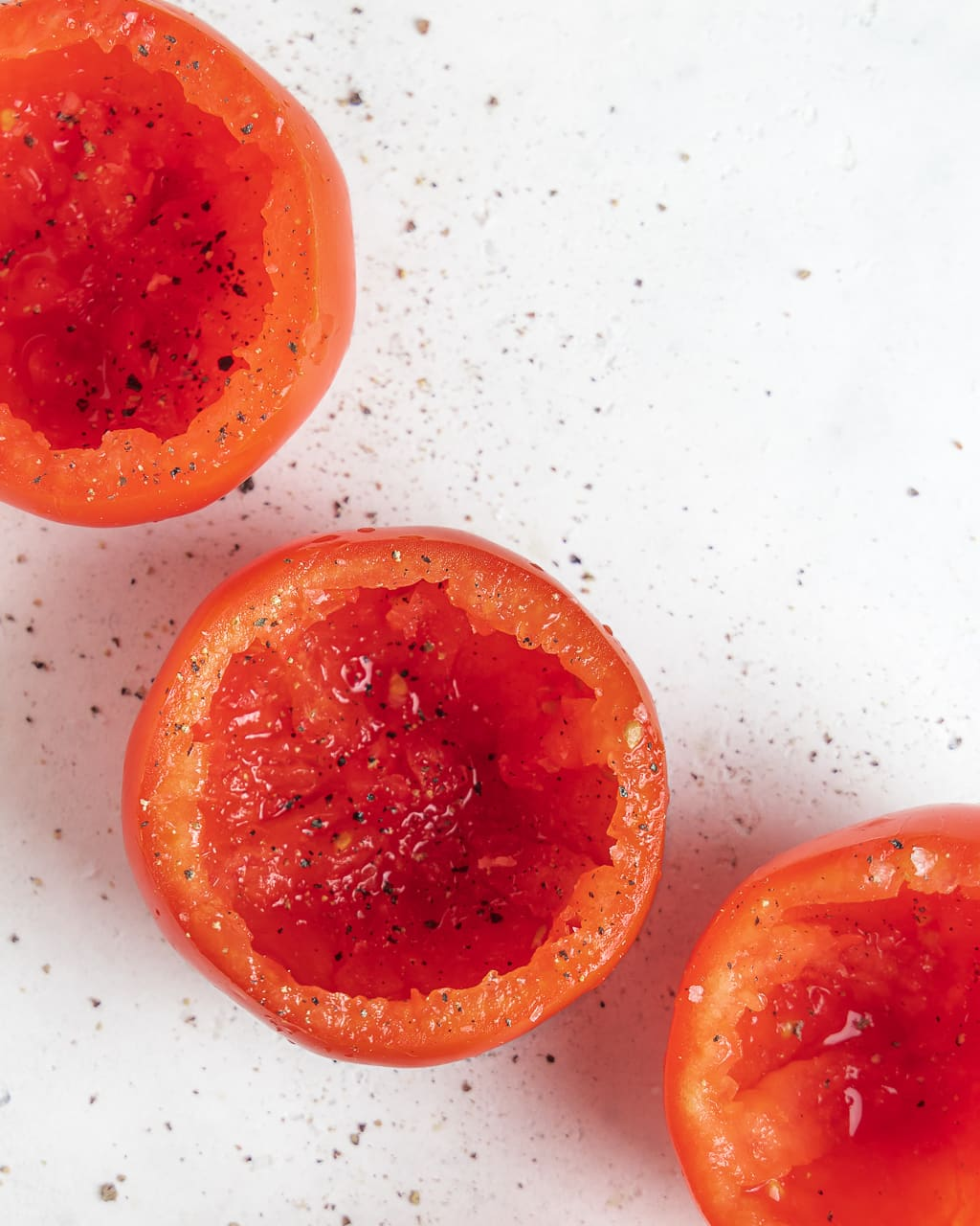 hollowed out tomatoes with salt and pepper