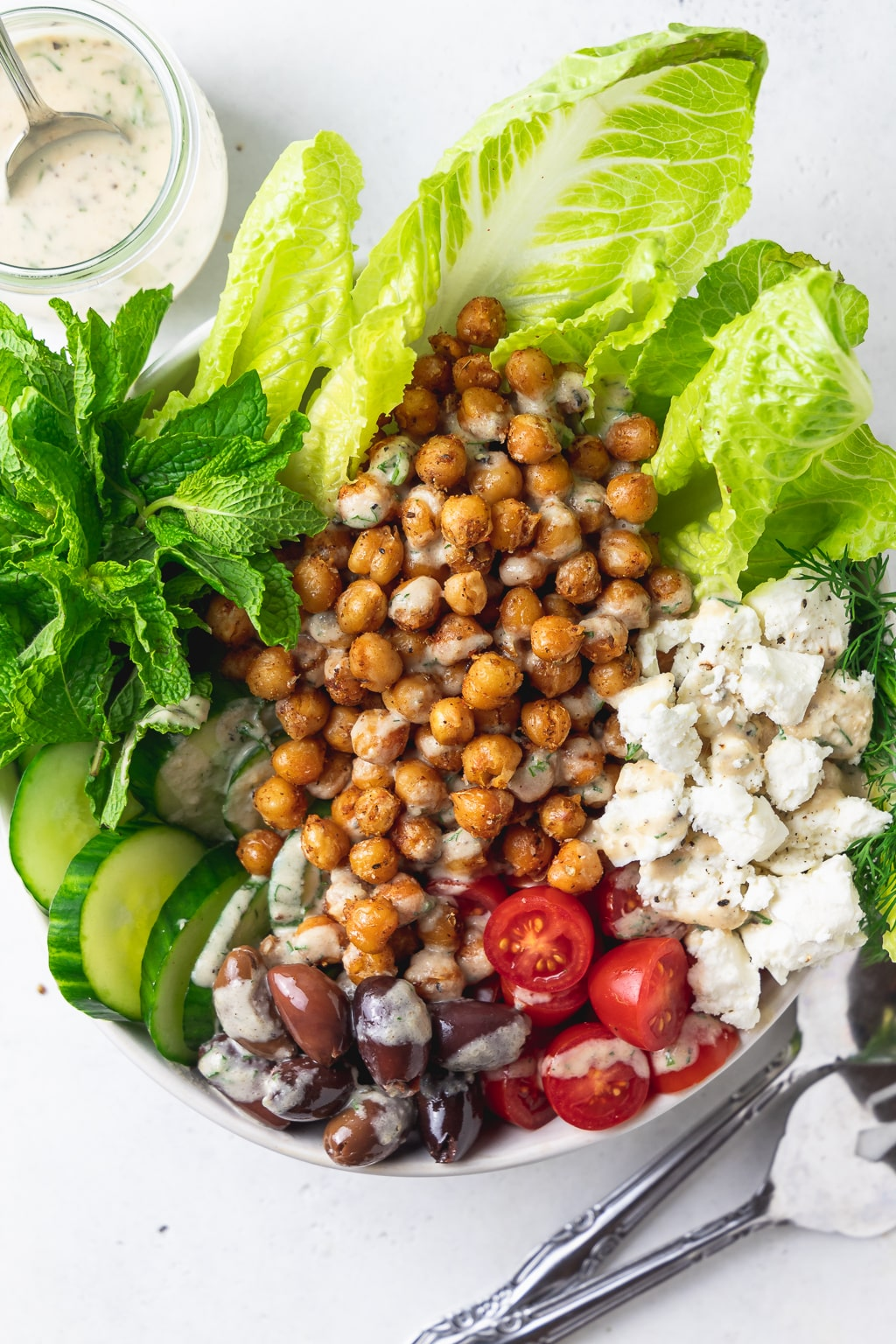 overhead of spiced chickpea greek salad with tahini vinaigrette