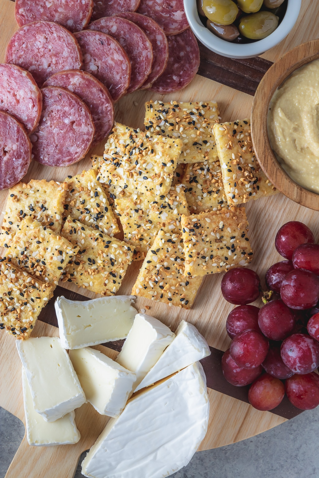 cheesy everything crackers on a cheese board