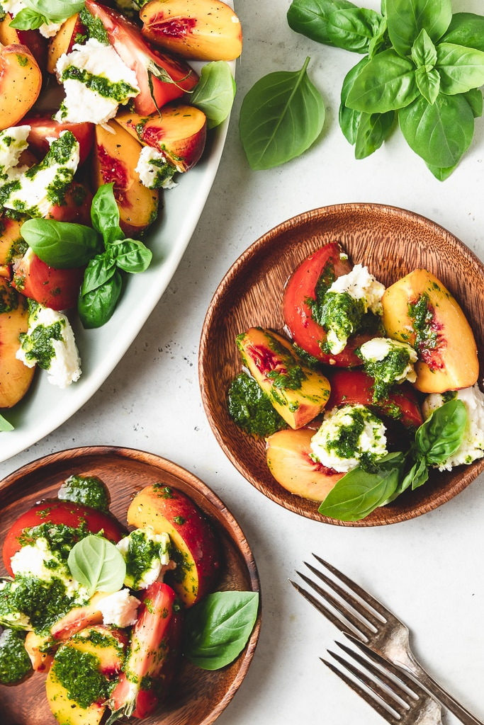 peach caprese salad on wood plates with basil