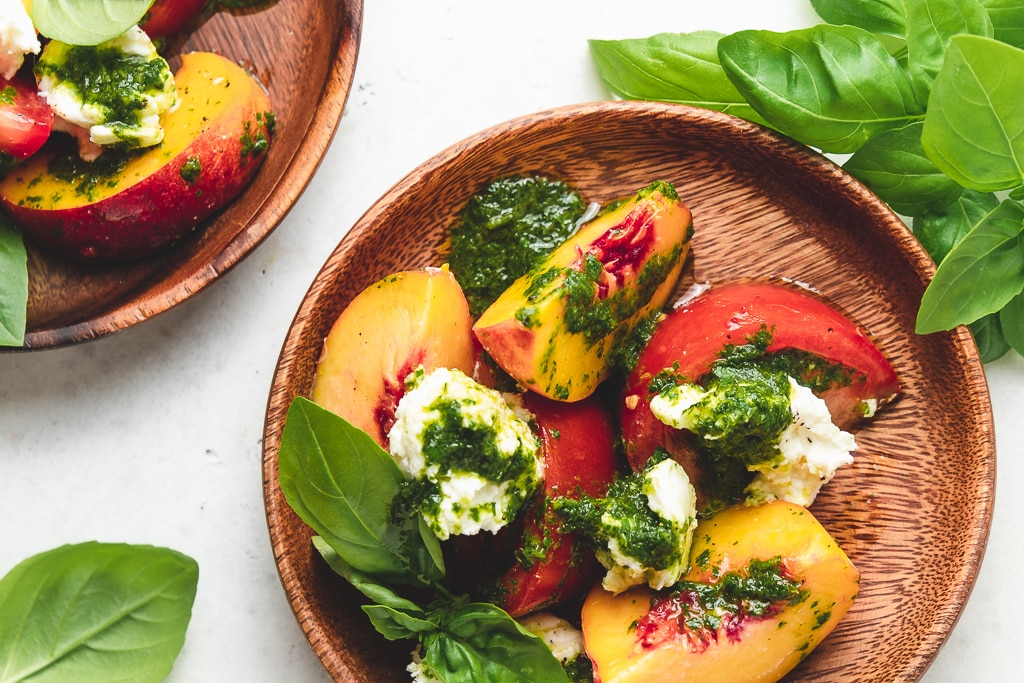 peach and tomato salad on wood plate with basil