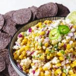 bowl of spicy charred corn dip with blue corn chips