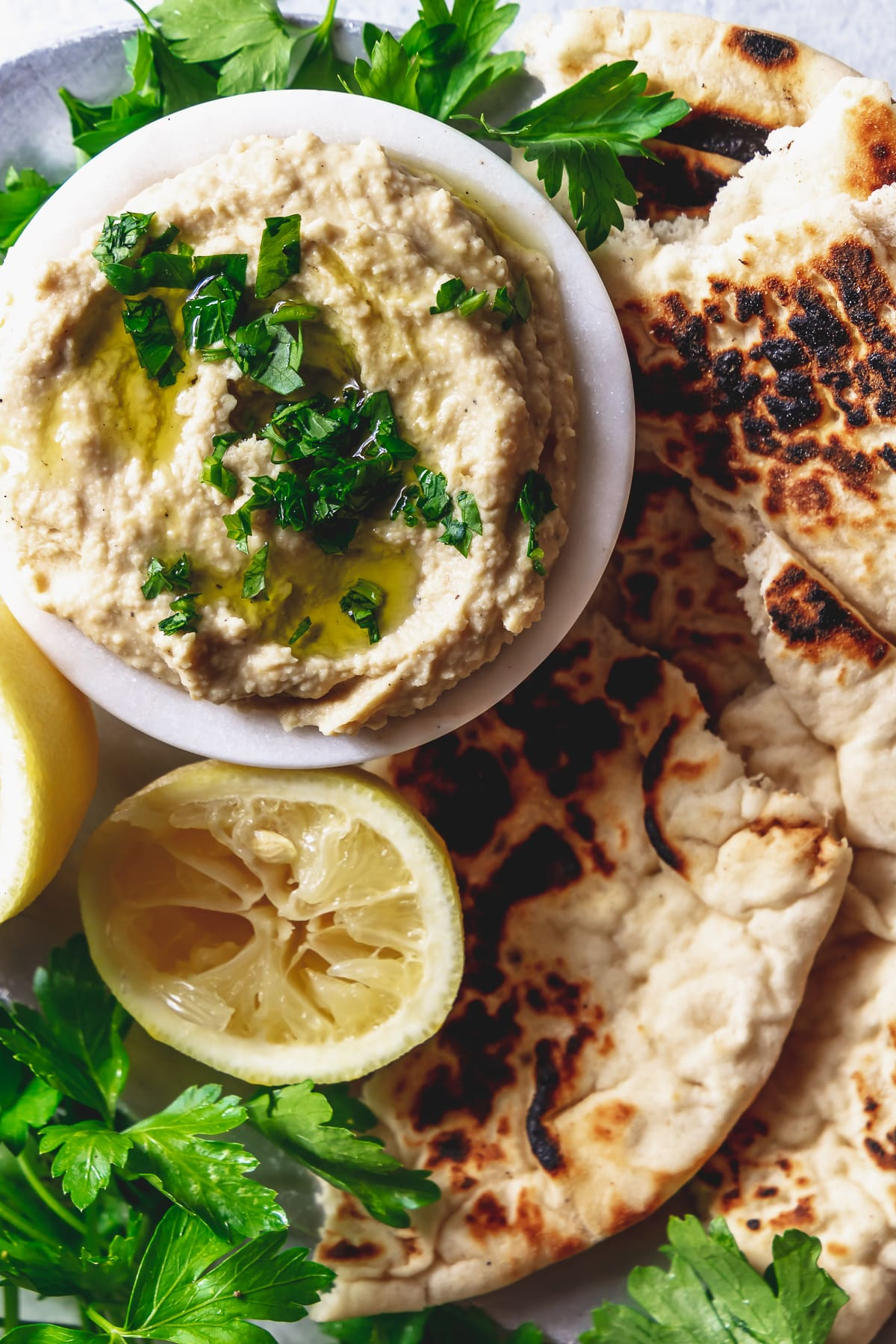 lemony hummus in a small bowl with torn flatbread