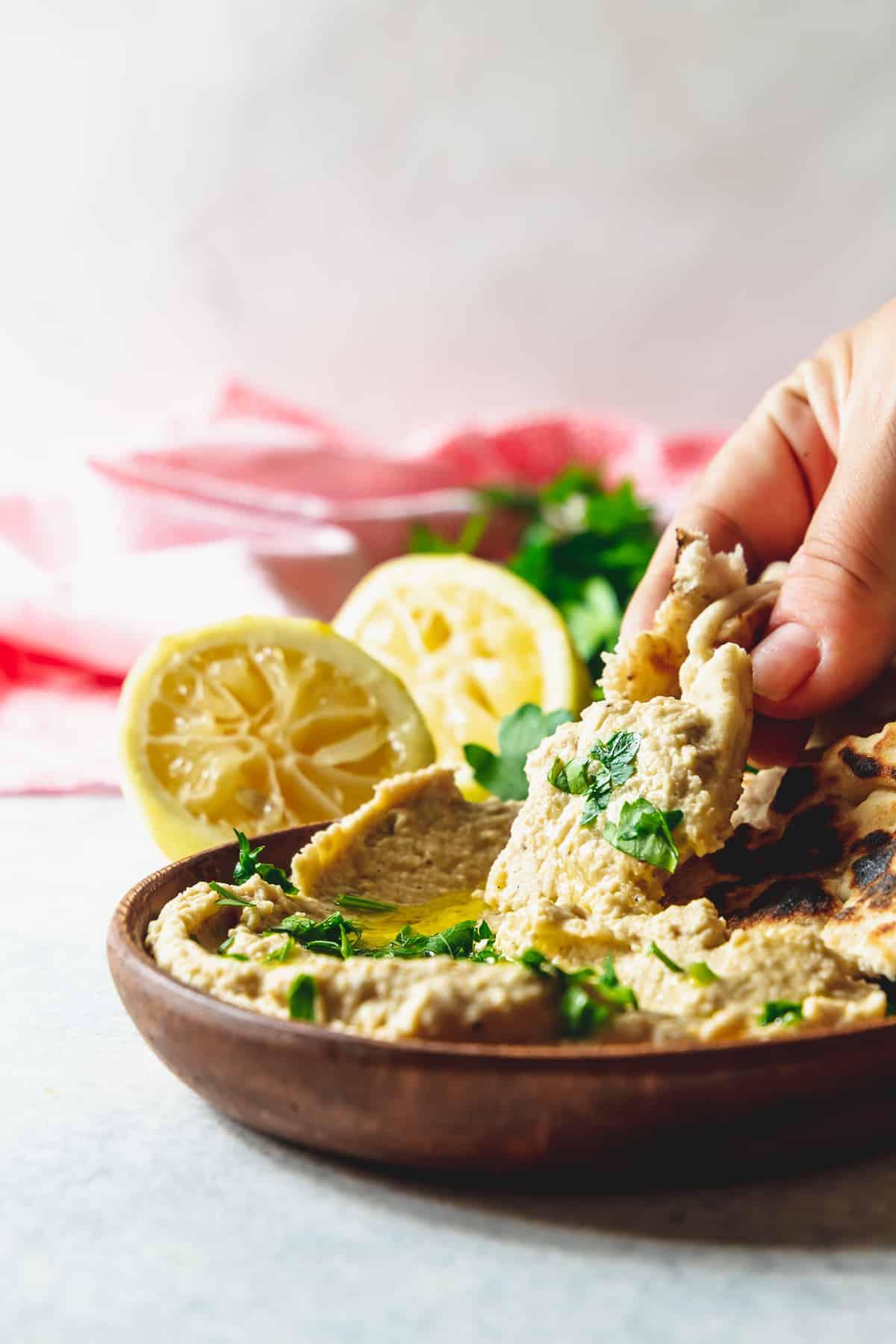 easy lemon hummus on a wood plate with flatbread