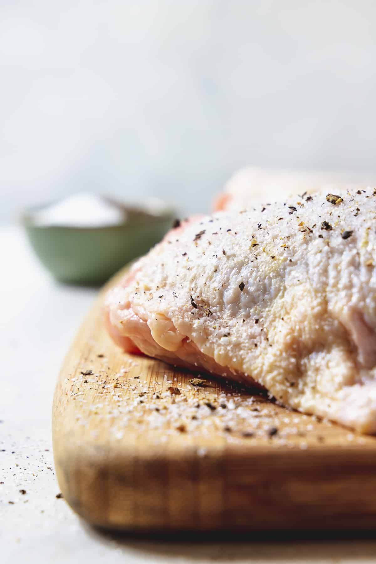 raw chicken thigh with salt and pepper