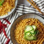 bowls of spicy peanut ramen with pickled cucumbers