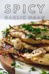 Spicy garlic naan on a wood and marble board