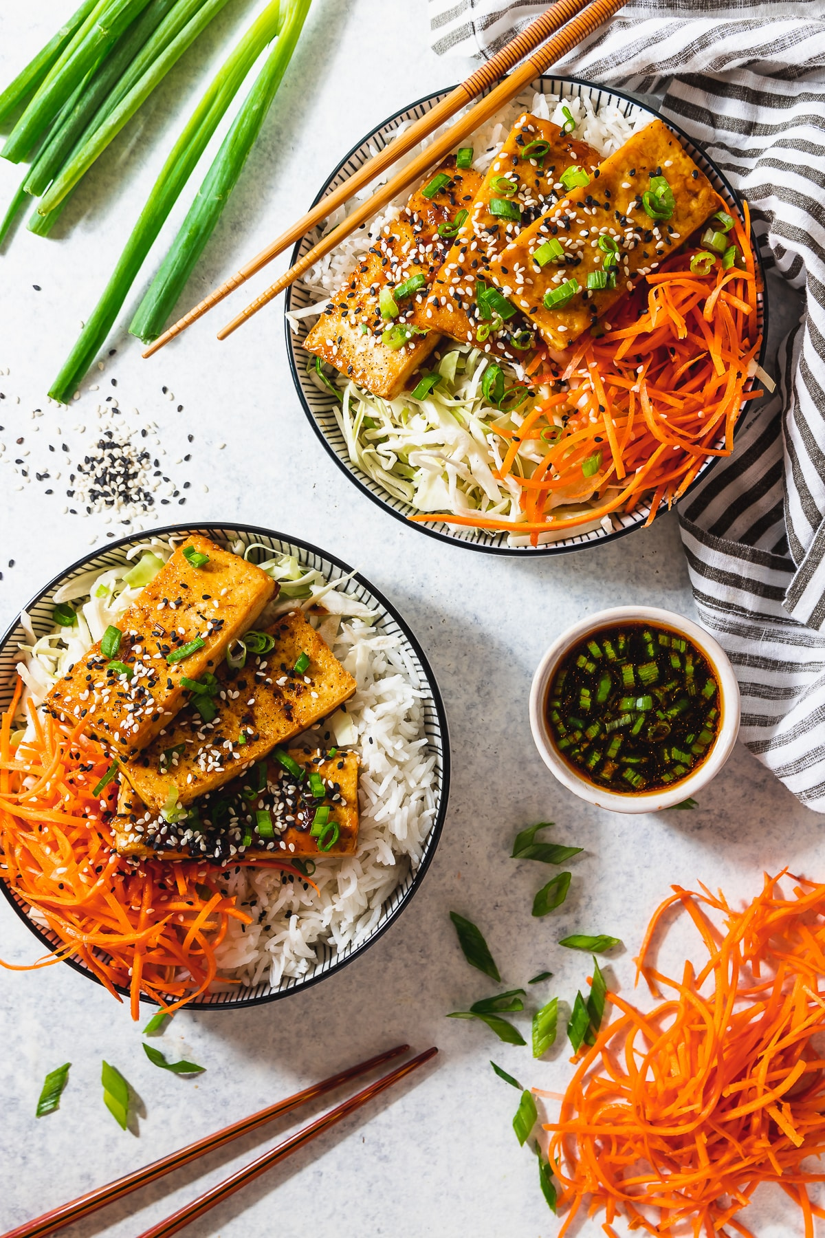 sesame tofu bowls with sauce, napkin and chopsticks