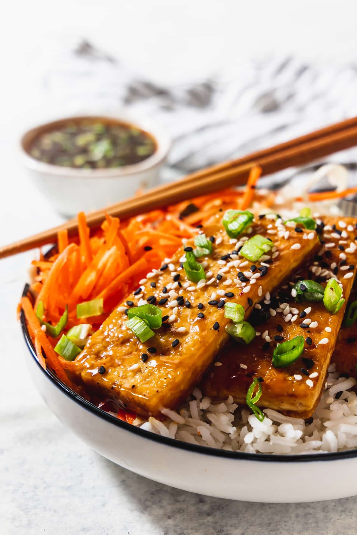 sesame tofu bowl with sauce, napkin and chopsticks