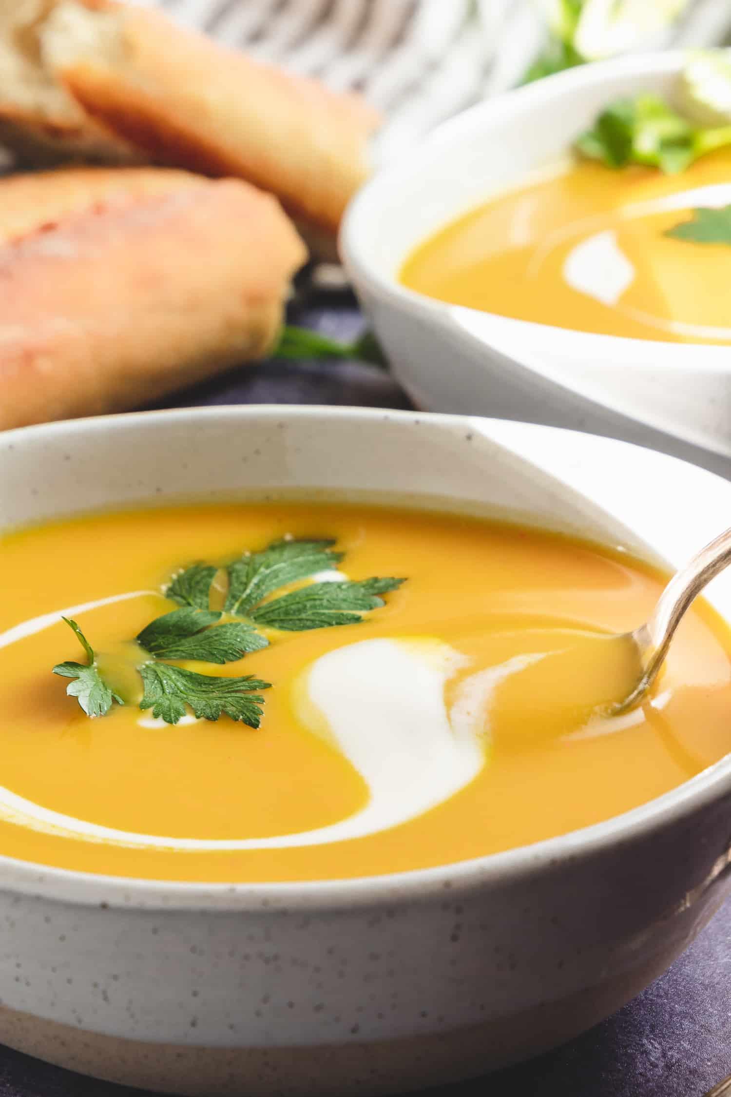 curry cauliflower soup in bowls with yogurt swirl