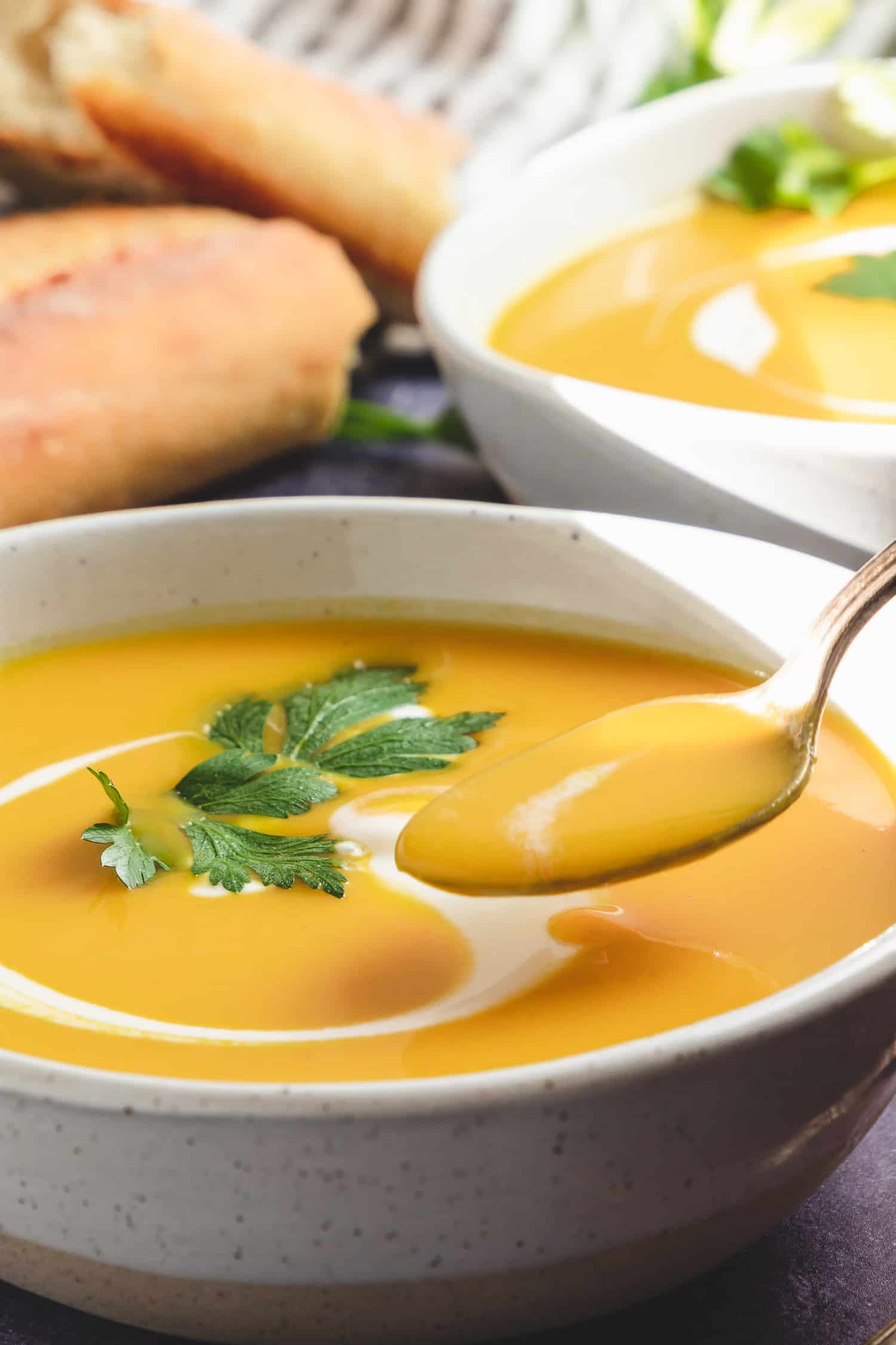spoonful of curried cauliflower soup in bowls with yogurt swirl
