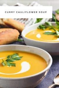 curried cauliflower soup in bowls with yogurt swirl