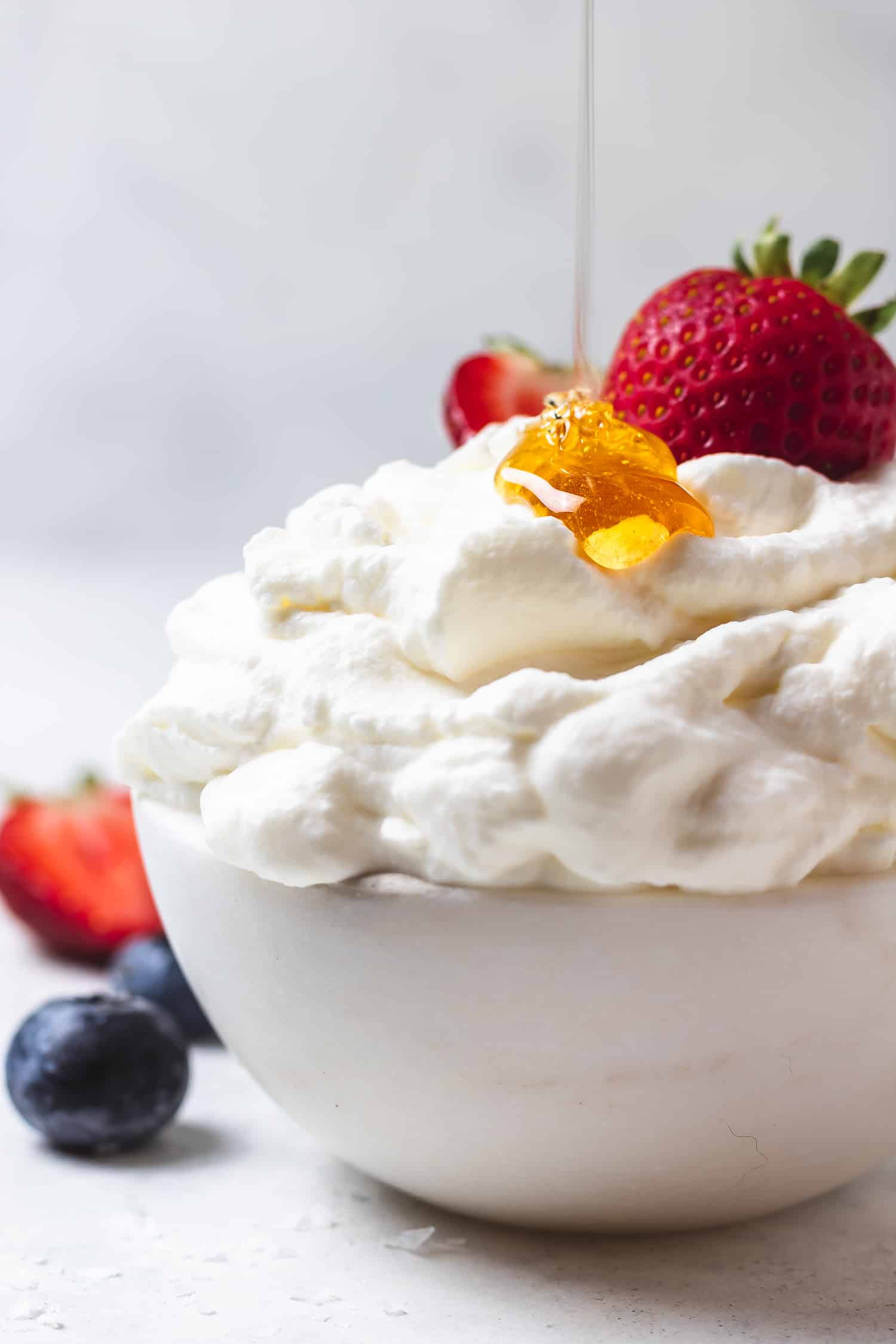 bowl of salted honey whipped cream with honey drizzle and berries