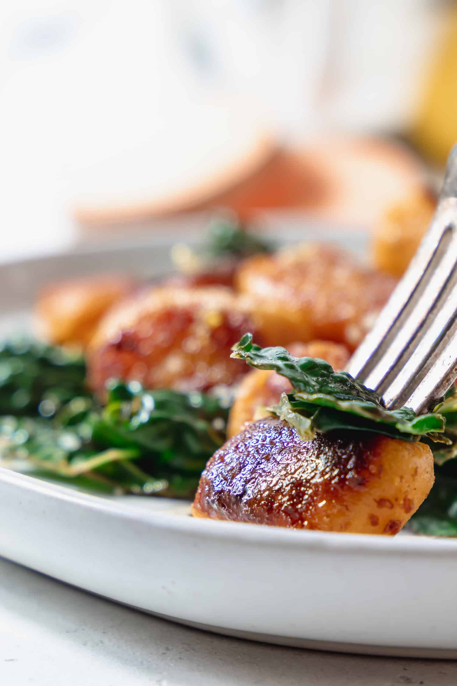 bite of sweet potato gnocchi with kale and brown butter
