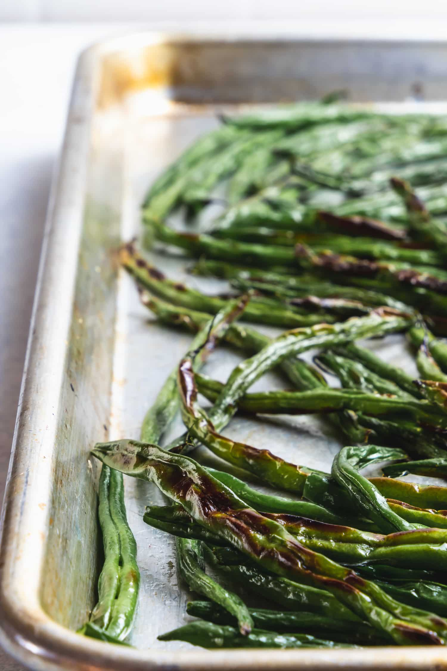 charred green beans on a sheet pan