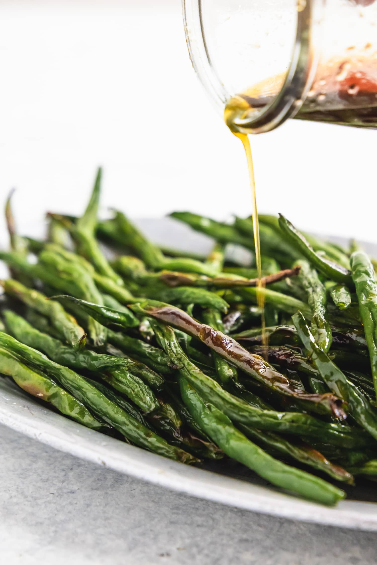 maple soy sauce pouring onto charred green beans
