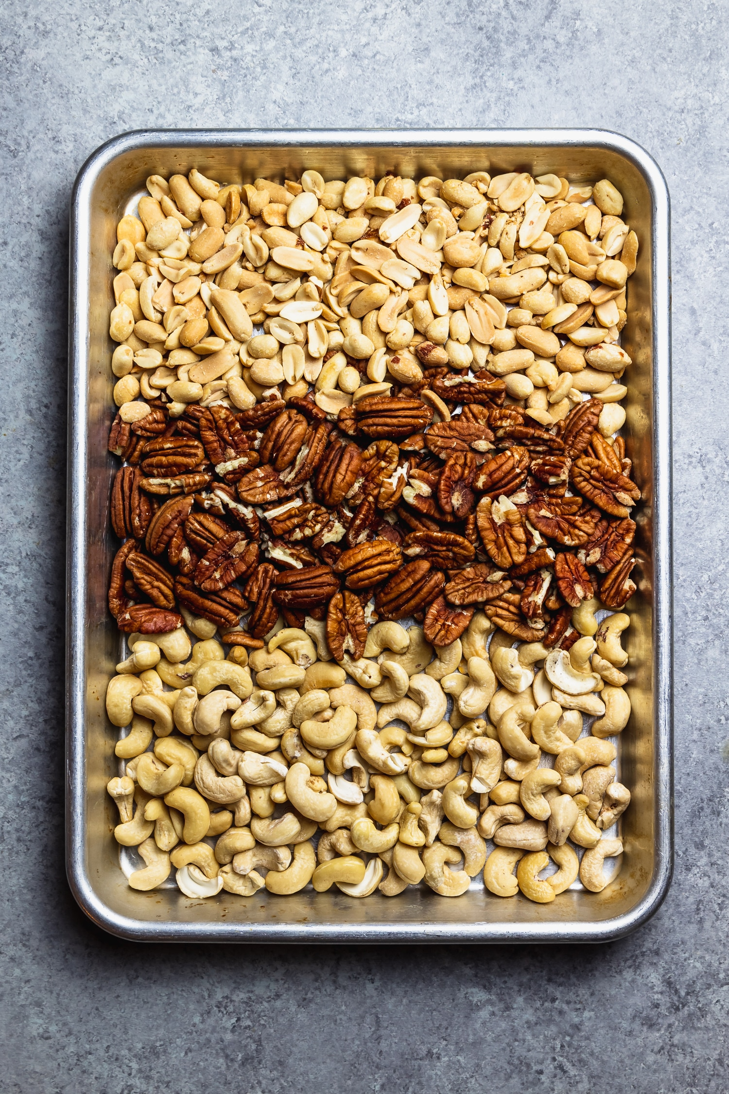 pecans, peanuts, and cashews on a rimmed baking sheet