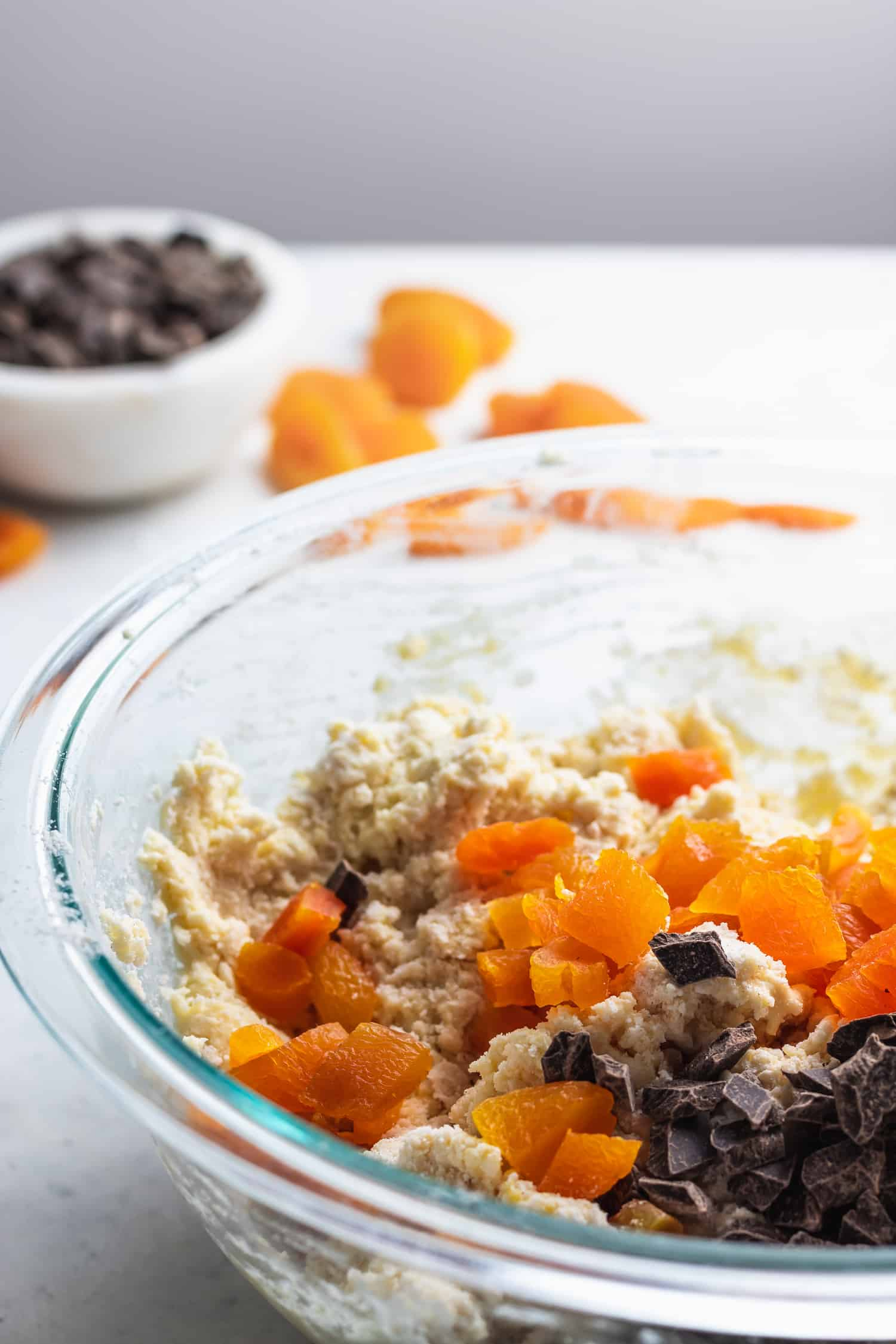 apricots and chocolate chunks added to scone dough in a glass bowl