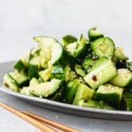 smashed cucumber salad on a silver plate with chopsticks