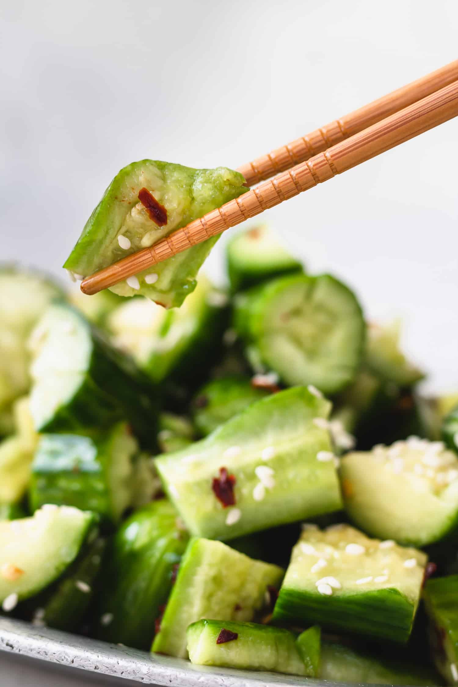 chopsticks holding up a piece of cucumber salad