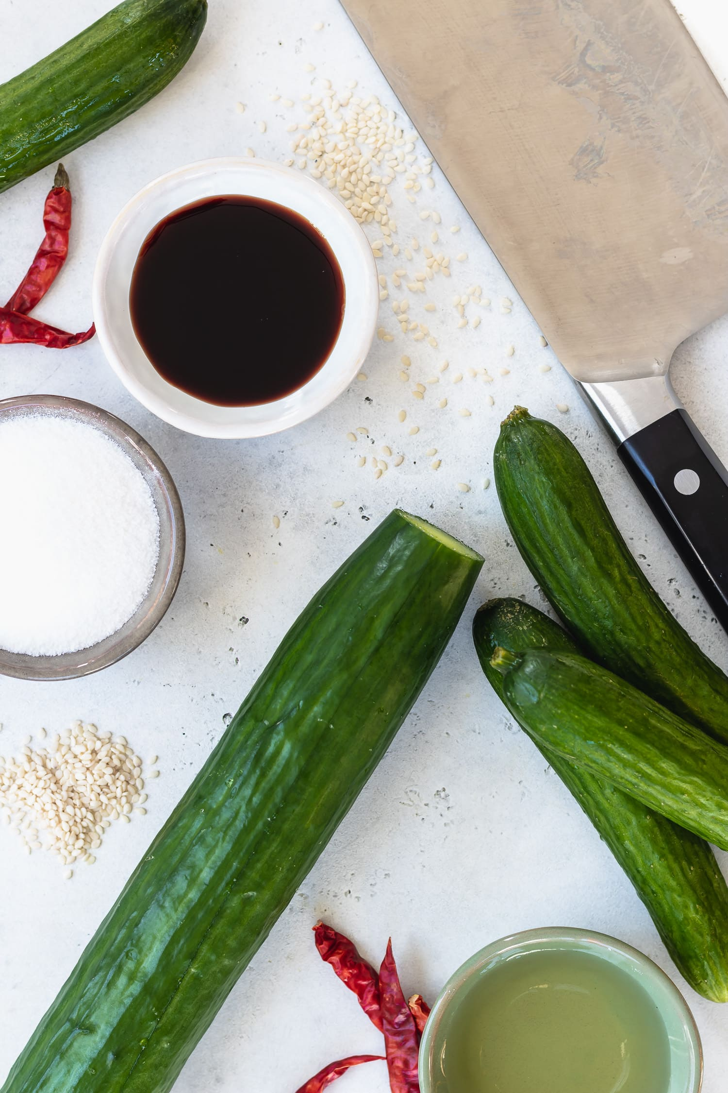 cucumbers, ingredients, and a cleaver