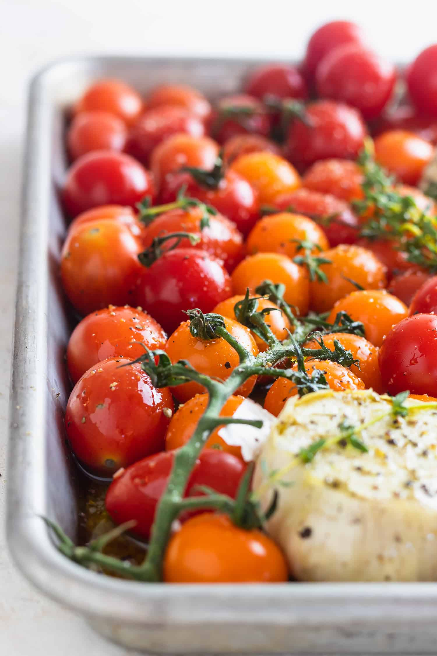 tomatoes, thyme and garlic on a sheet pan with salt pepper and olive oil