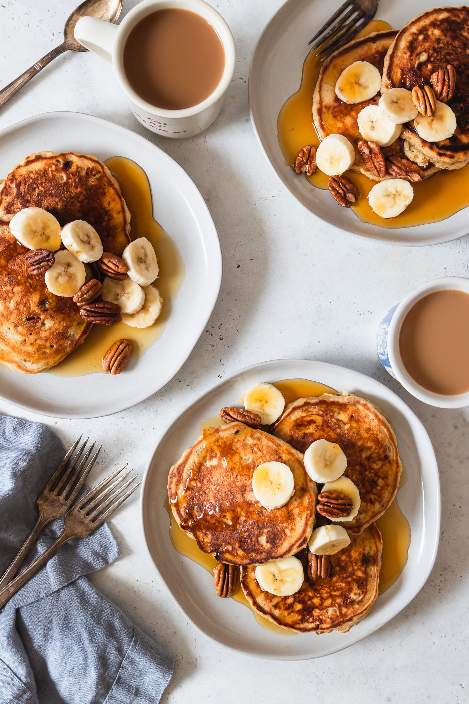 banana bread pancakes on three plates with coffee