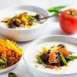 loaded cauliflower soup with fixings in two bowls