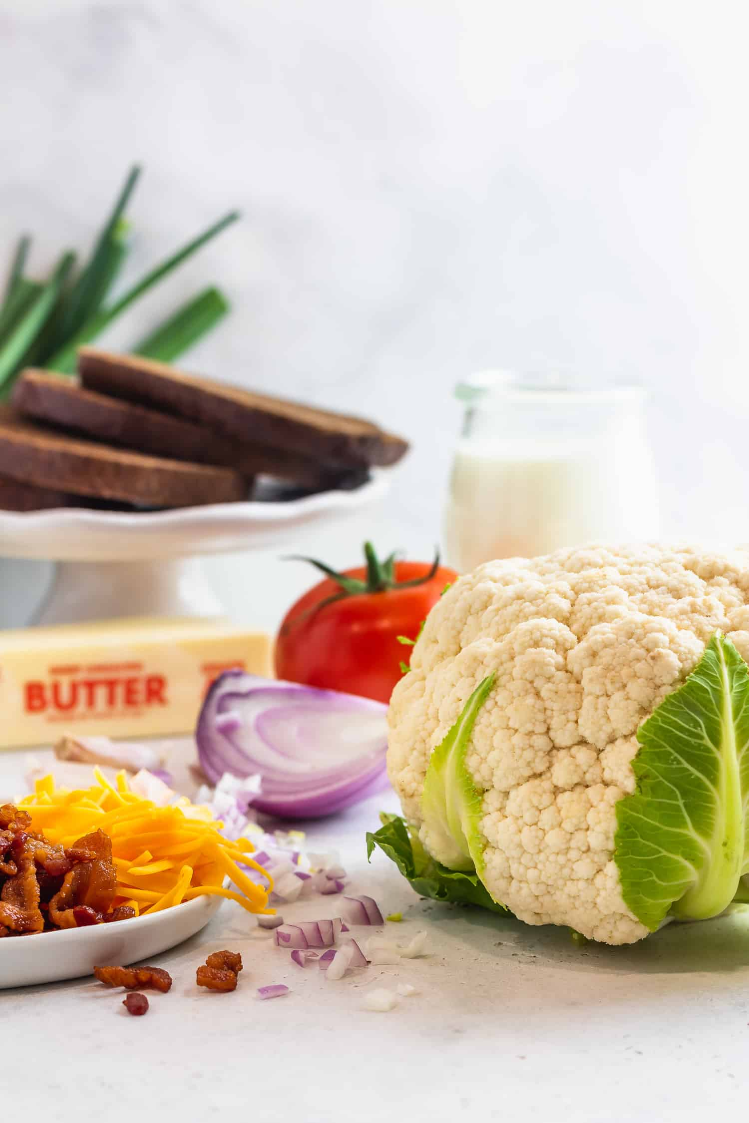 cauliflower, red onion, tomato, butter, cream, cheese, bacon, and pumpernickel bread