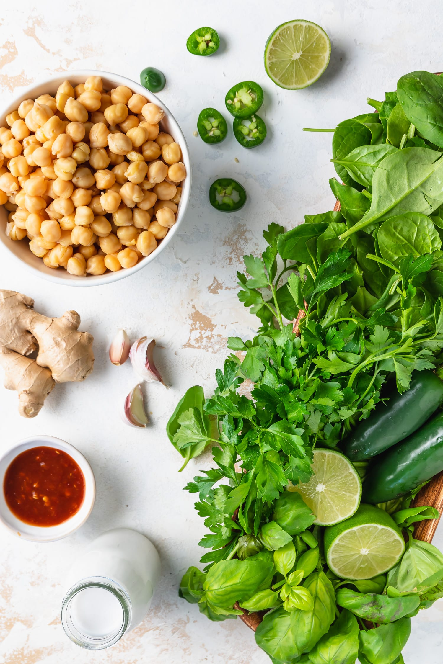ingredients - chickpeas, limes, herbs, jalapenos, ginger, sambal, coconut milk on light background