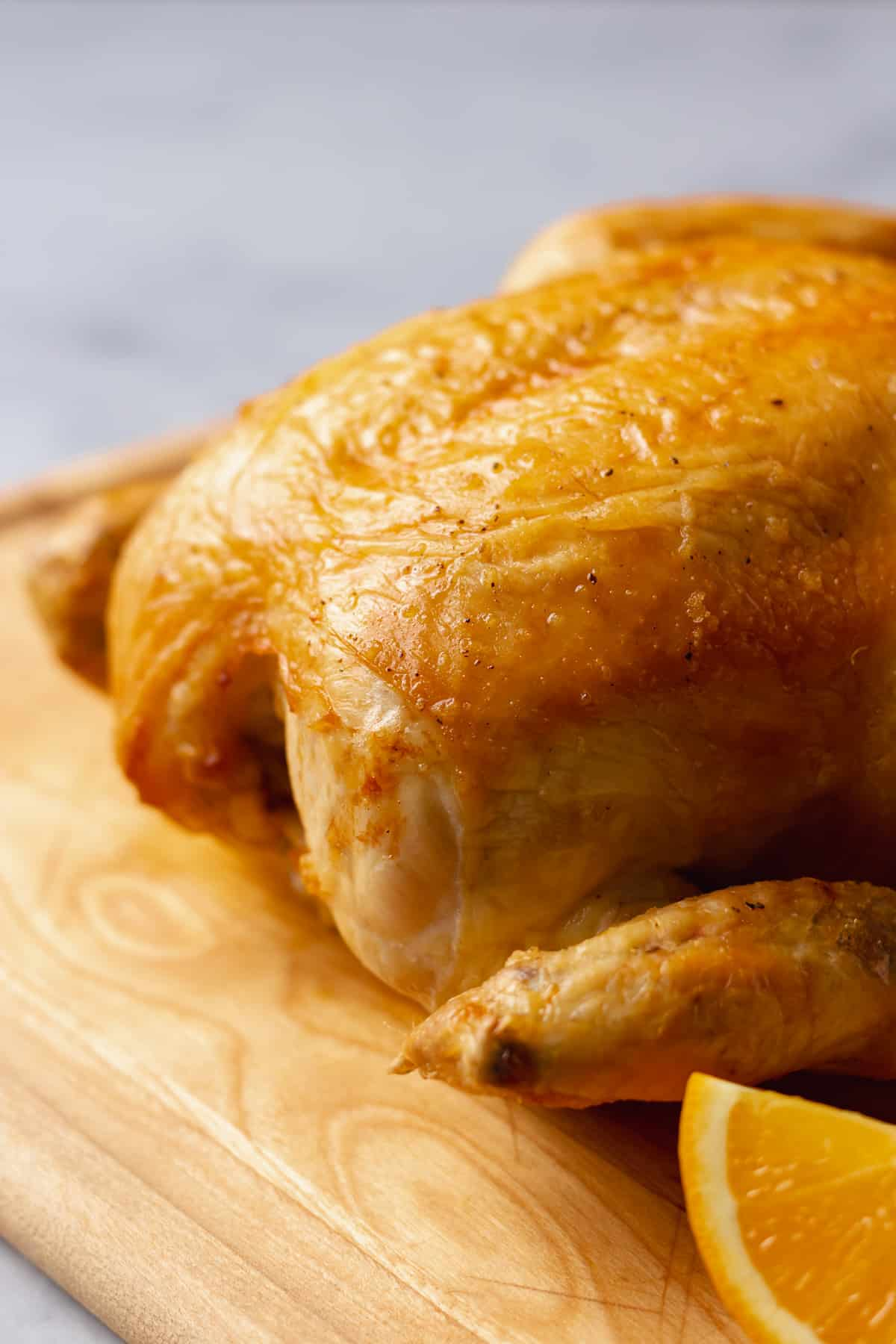 whole roasted chicken on a wooden cutting board