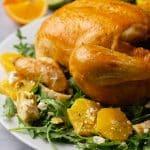 Whole roast chicken on a platter with arugula and artichoke citrus salad